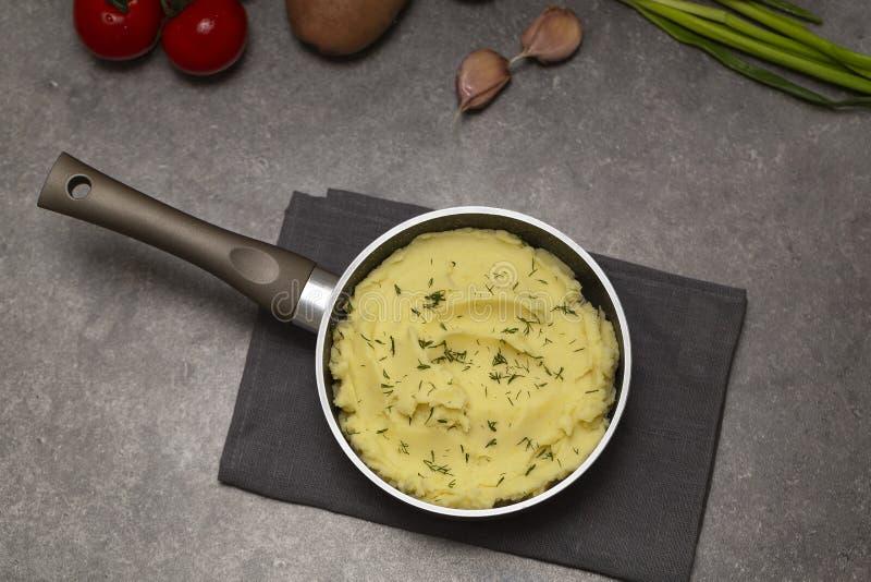 Fijngestampte aardappels in een steelpan op donkere achtergrond, hoogste mening Heerlijke hete fijngestampte aardappel met boter  royalty-vrije stock fotografie