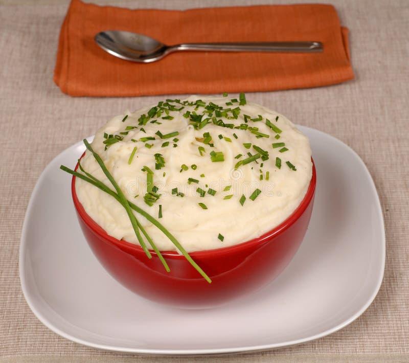 Fijngestampte aardappels met bieslook in een rode kom stock foto