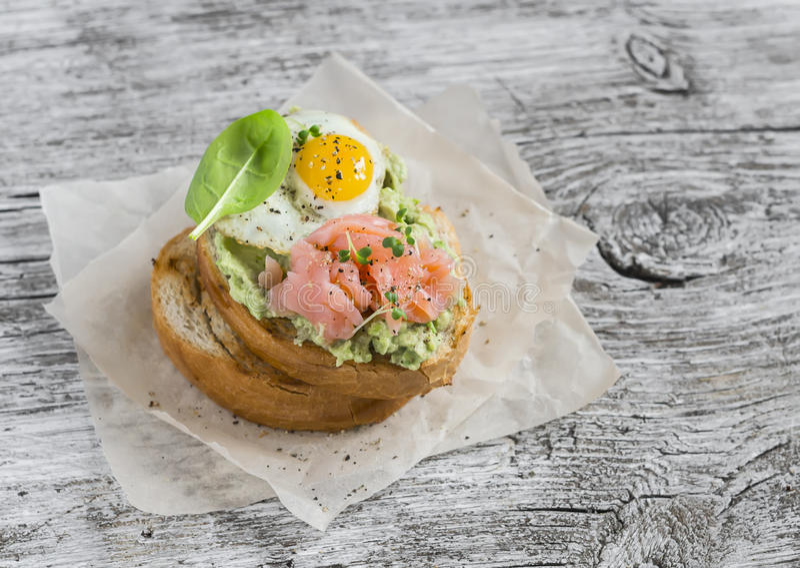 Fijngestampte avocadosandwich met gerookte zalm en gebraden kwartelsei Een heerlijke ontbijt of een snack stock afbeeldingen