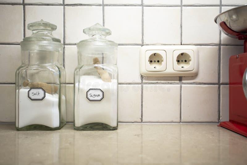 Fijo nostálgico de la cocina retro con dos jarras de sal y azúcar en el mostrador, enfoque selectivo en la sal imagen de archivo libre de regalías