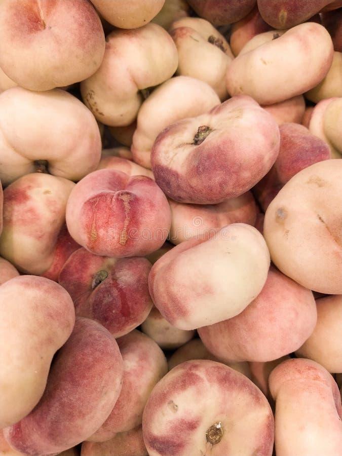 Fikontr?dpersika Saturn persikor plana persikor skördar många persikor Ny frukt på bönders marknad: persikor fikonträdpersikabakg arkivfoto