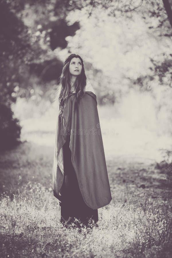 Fiktionkvinna i kappa i skog arkivbilder