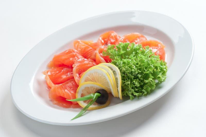 Filé av den röda fisken på en platta med gräsplaner och citronen royaltyfria foton
