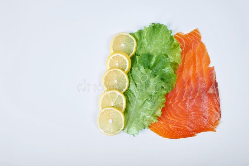 Filé av den rökte röda fisken med citronen och örter, isolerad vit bakgrund royaltyfria bilder