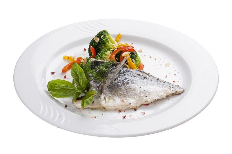 Filé av doradoen med ångade grönsaker På en vit plätera royaltyfria foton