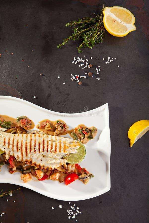 Filé av seabassen med grönsaker royaltyfri fotografi