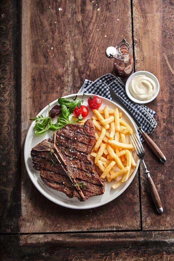 Filé de T-bone magra grelhado com batatas fritas douradas fotografia de stock royalty free