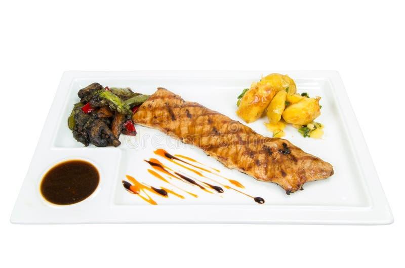 Filén bakade fisken med grillade potatisar, lökar och ångade grönsaker royaltyfria bilder