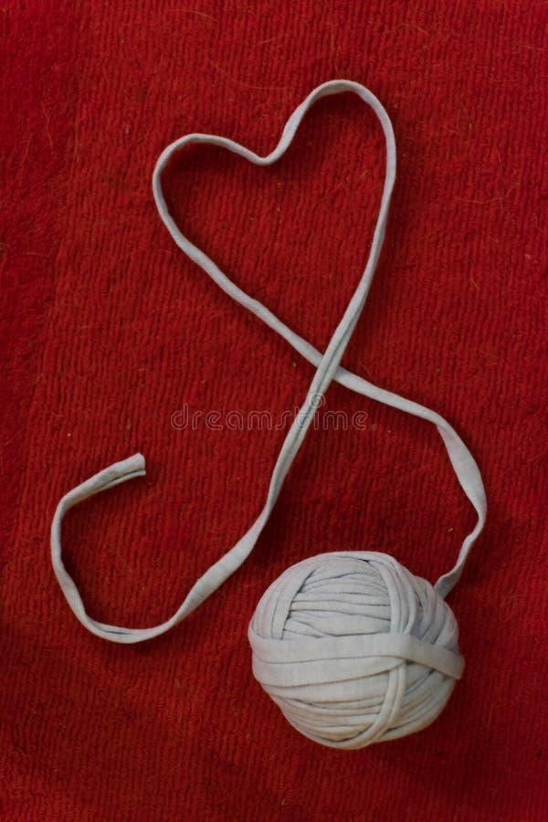 Fil de laine dans le symbole de forme de coeur avec le crochet de crochet image stock