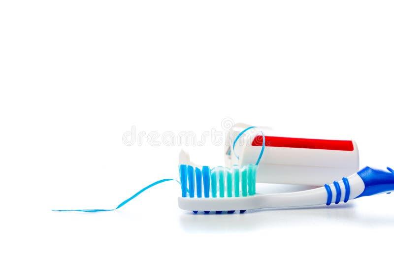 Fil dentaire et brosse à dents sur un fond d'isolement photos stock