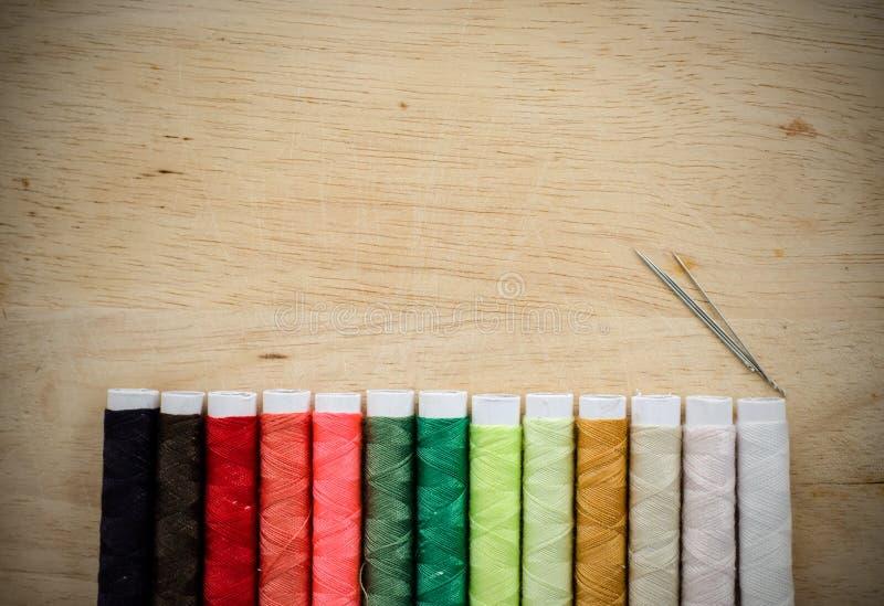 Fil et aiguilles de couture sur le fond en bois photo libre de droits