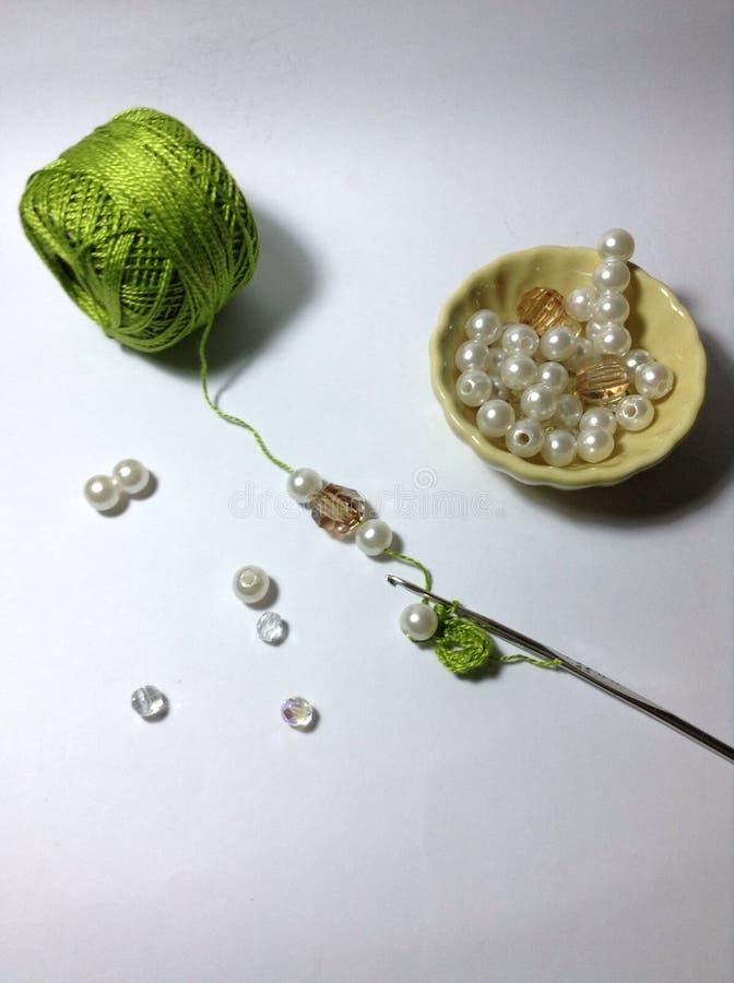 Fil et crochet de crochet de vert de travail de perle images stock