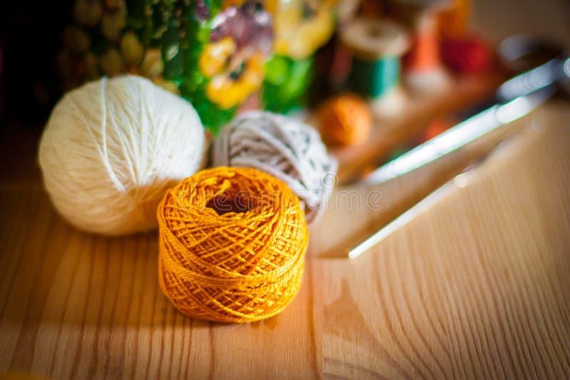 Fil jaune de crochet avec le fond d'outils de passe-temps sur la surface en bois photo stock