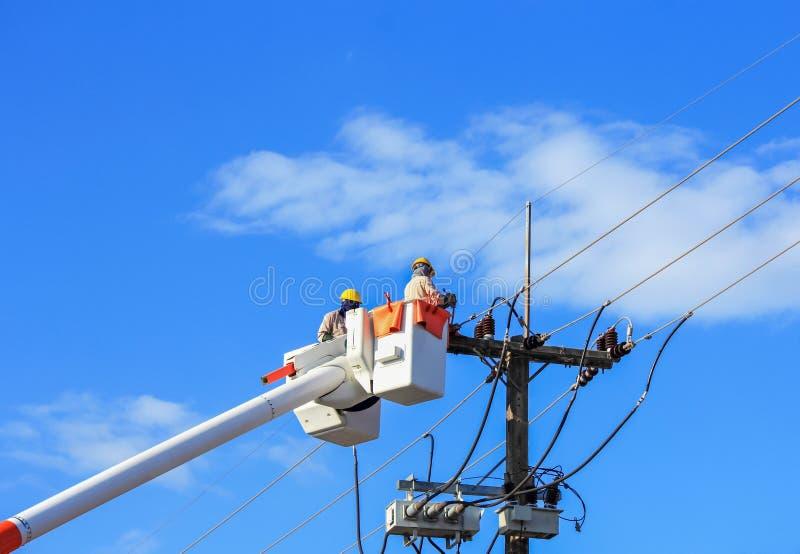 Fil travaillant de réparation d'électricien de la ligne électrique photographie stock libre de droits