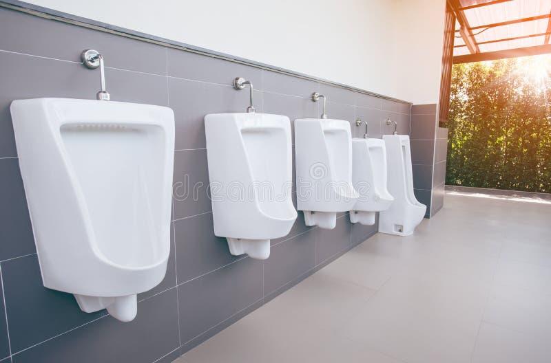 Fila alta vicina della toilette pubblica degli uomini all'aperto degli orinali, orinali bianchi del primo piano nel bagno degli u fotografia stock