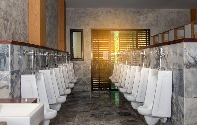 Fila blanca del orinal en el lavabo moderno interior, fondo de los orinales fotos de archivo