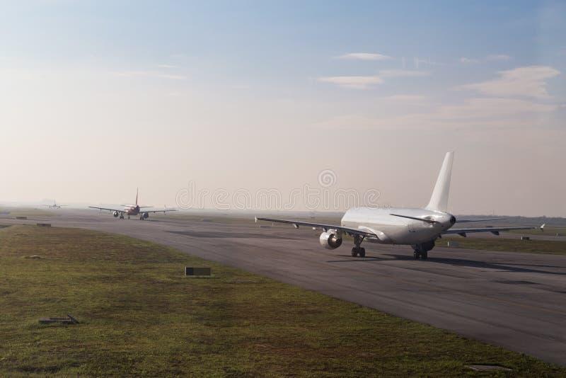 Fila comercial do avião que taxiing para decolar na pista de decolagem fotos de stock royalty free