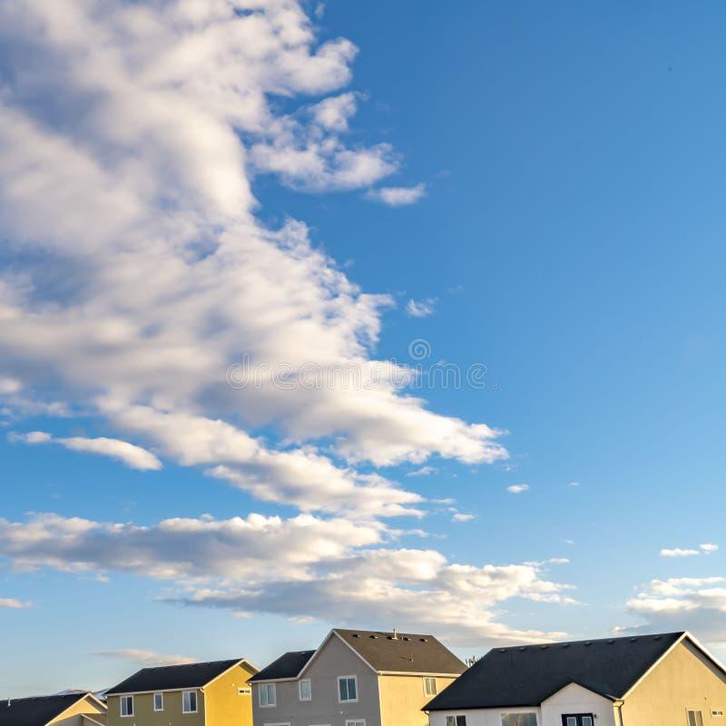Fila cuadrada clara de casas debajo de un cielo azul vibrante con las nubes mullidas en un día soleado foto de archivo
