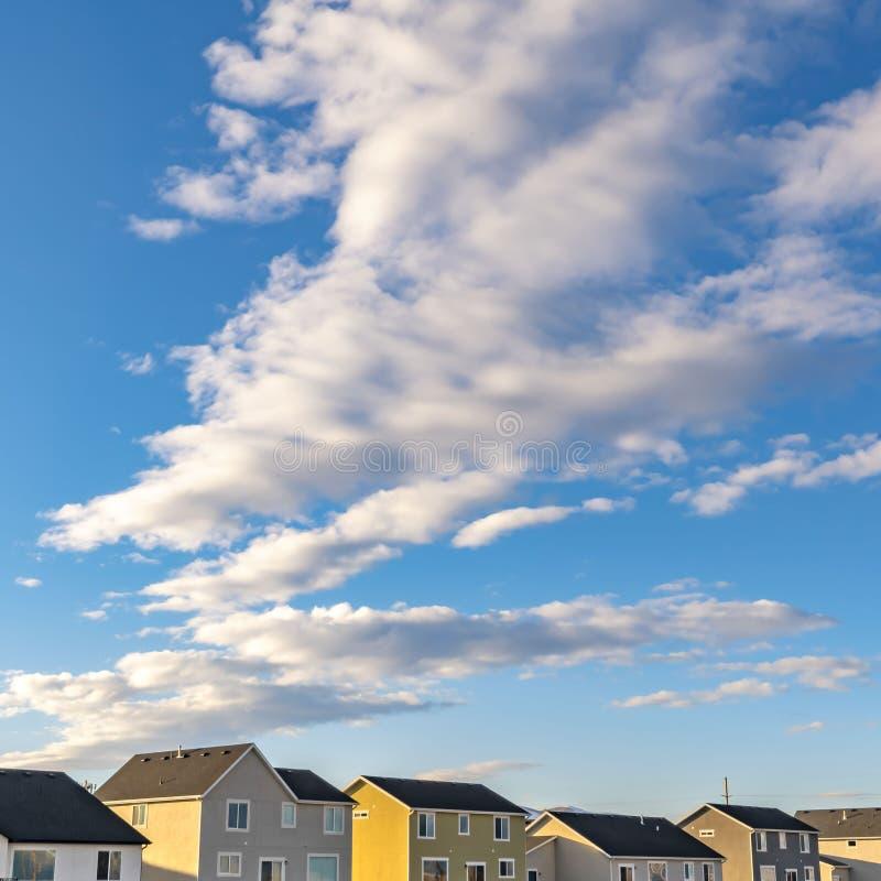 Fila cuadrada de casas debajo de un cielo azul vibrante con las nubes mullidas en un día soleado fotografía de archivo
