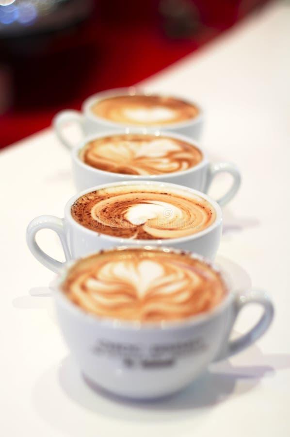 Fila de 4 tazas del cappuccino fotografía de archivo
