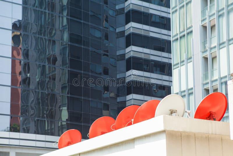 Fila de antenas parabólicas rojas en el edificio imagen de archivo libre de regalías