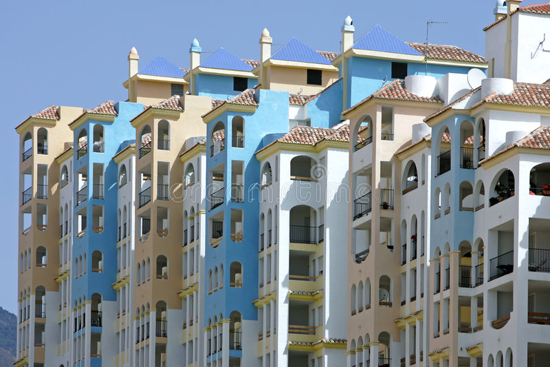Fila de apartamentos asoleados coloridos en España fotos de archivo