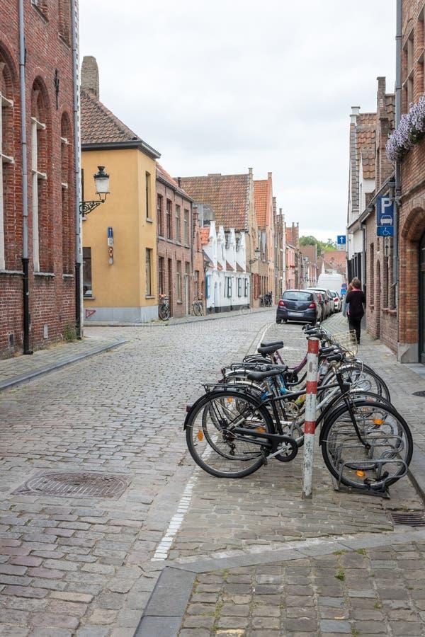 Fila de bicicletas en la calle Cobblestone en Brujas fotos de archivo
