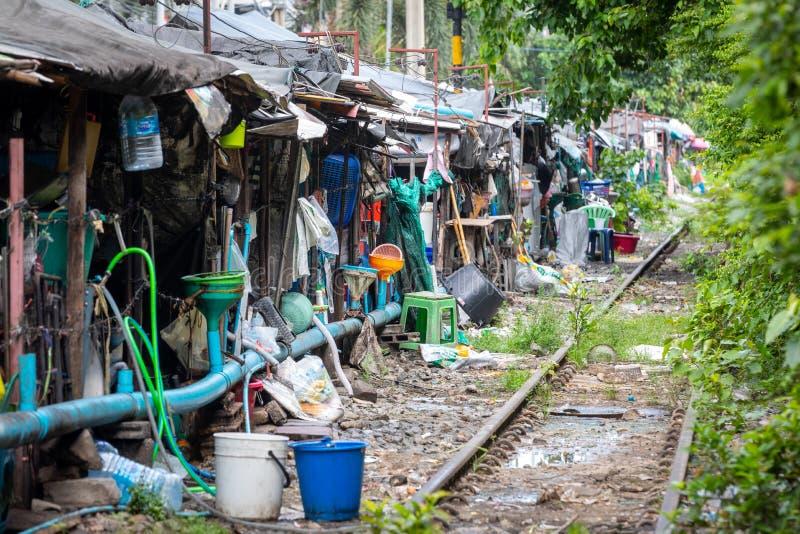 Fila de cabañas con pequeñas empresas al lado de las vías de un tren en Bangkok central en Tailandia foto de archivo libre de regalías