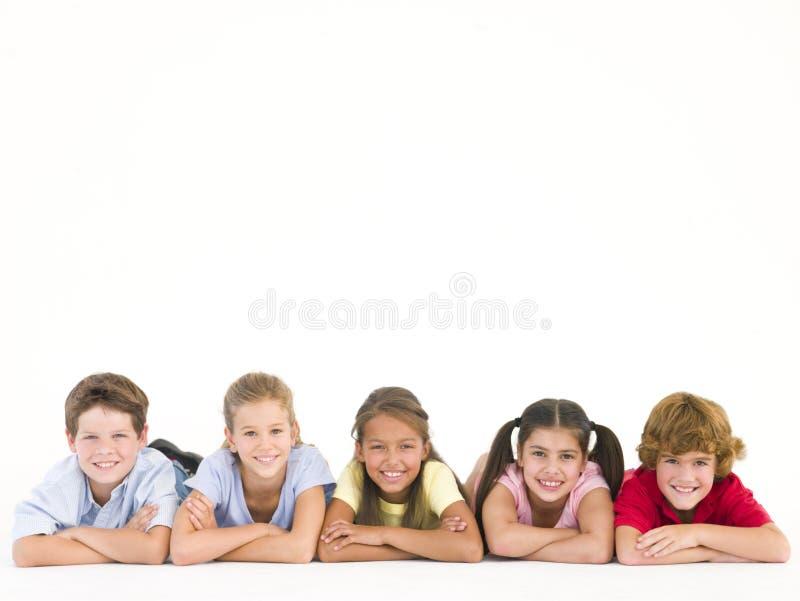 Fila de cinco amigos que mienten abajo sonriendo