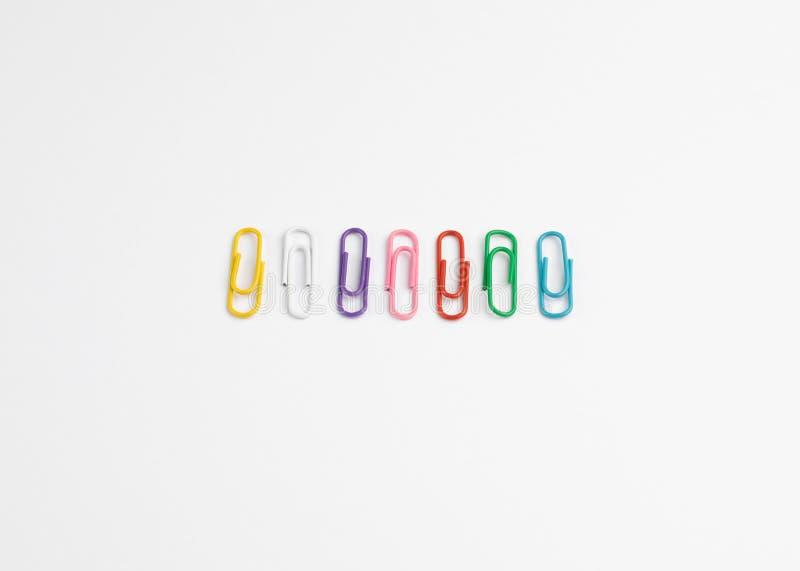 Fila de clips de papel multicolores en un fondo blanco imágenes de archivo libres de regalías