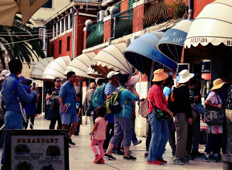 Fila de espera dos turistas a comprar fotos de stock