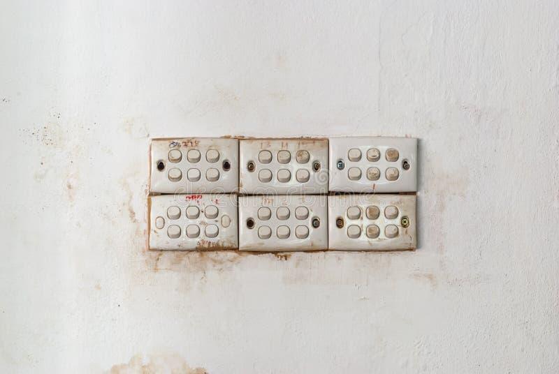Fila de interruptores de la luz sucios en el muro de cemento manchado imagen de archivo libre de regalías