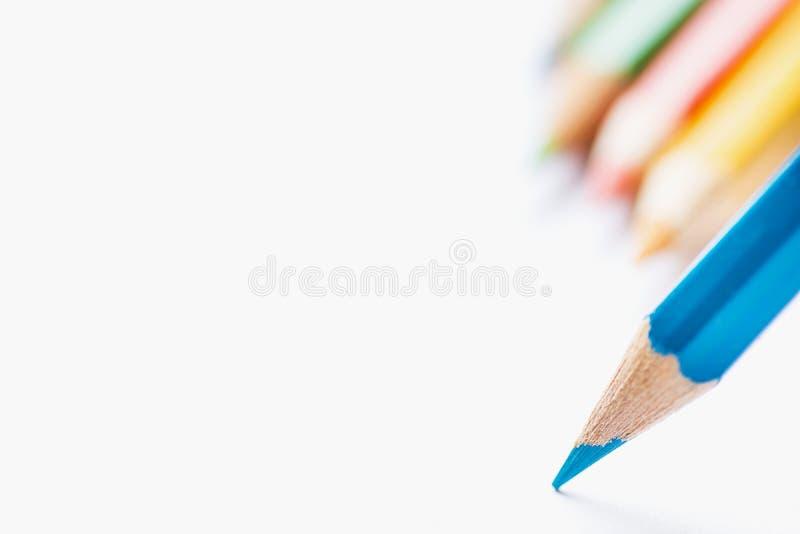 Fila de lápices multicolores en el solo lápiz agudo azul del fondo que señala con extremidad al Libro Blanco en blanco Principio  imagenes de archivo