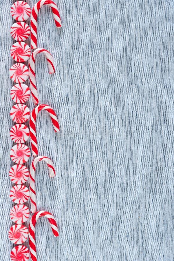 Fila de la frontera puesta plana de los bastones de caramelo y de los caramelos del remolino de la hierbabuena fotografía de archivo libre de regalías