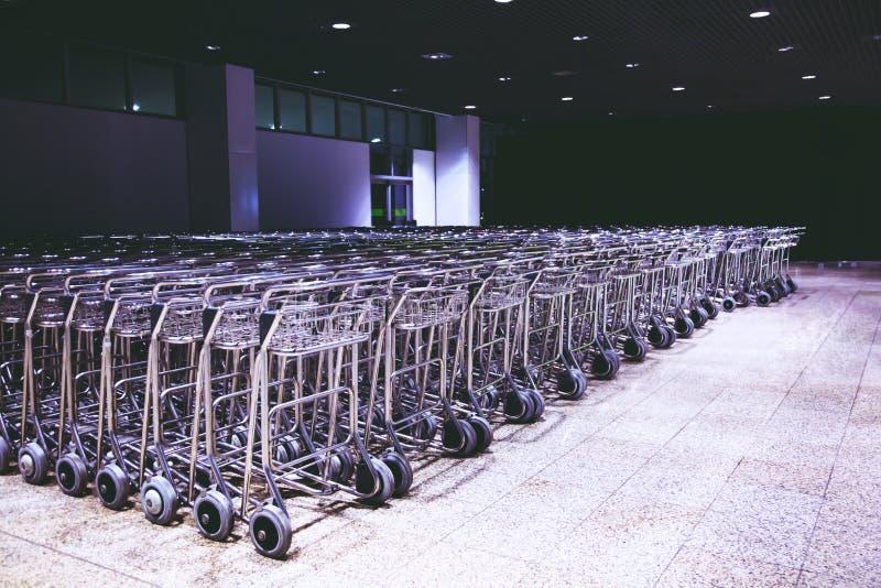 Fila de la gran cantidad de las carretillas de los carros del equipaje en el aeropuerto moderno internacional fotos de archivo libres de regalías