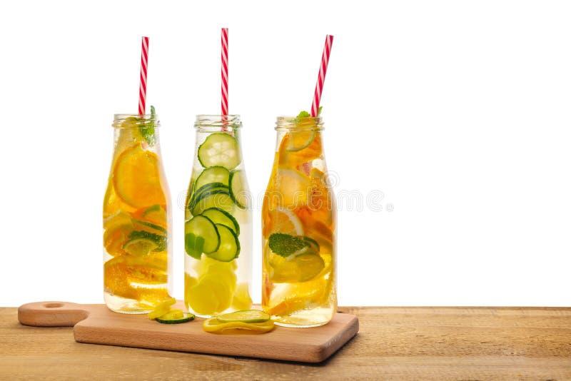 Fila de la limonada de las botellas con el limón, naranja, cal, menta de la ramita, cuc fotos de archivo