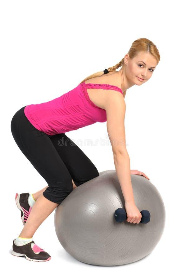Fila de la pesa de gimnasia del Uno-brazo en ejercicio de la bola de la aptitud de la estabilidad fotografía de archivo