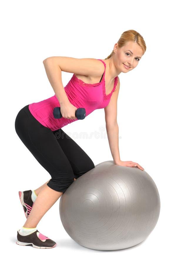 Fila de la pesa de gimnasia del Uno-brazo en ejercicio de la bola de la aptitud de la estabilidad foto de archivo