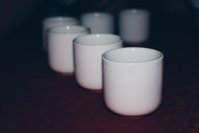 Fila de la taza de té de cerámica blanca en una tabla imagen de archivo