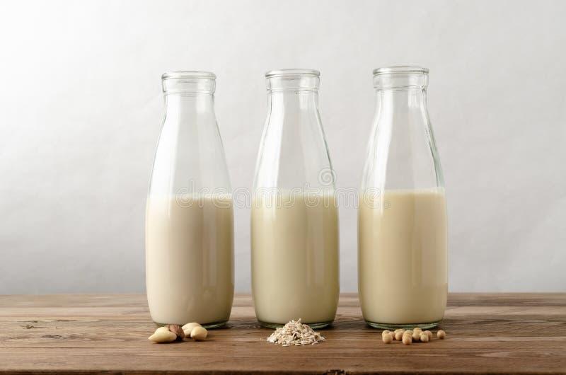 Fila de las alternativas libres de la leche de la lechería con los ingredientes en el Pla de madera fotografía de archivo libre de regalías