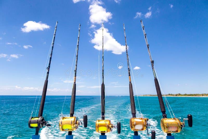 Fila de las cañas de pescar del mar profundo en el barco imagenes de archivo