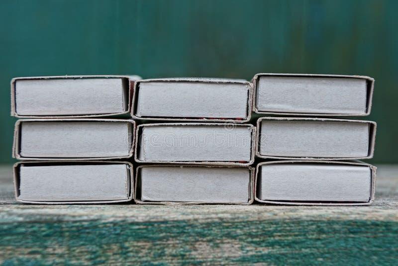 Fila de las cajas de cerillas del Libro Blanco en una tabla de madera imágenes de archivo libres de regalías