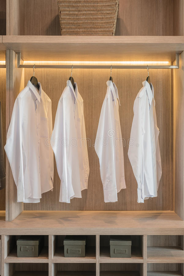 Fila De Las Camisas Blancas Que Cuelgan En El Carril Foto