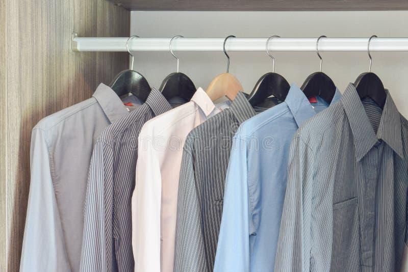 Fila de las camisas coloridas que cuelgan en guardarropa fotos de archivo libres de regalías