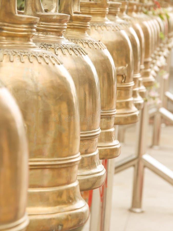 Fila de las campanas de cobre amarillo que cuelgan en templo tailandés imagen de archivo libre de regalías