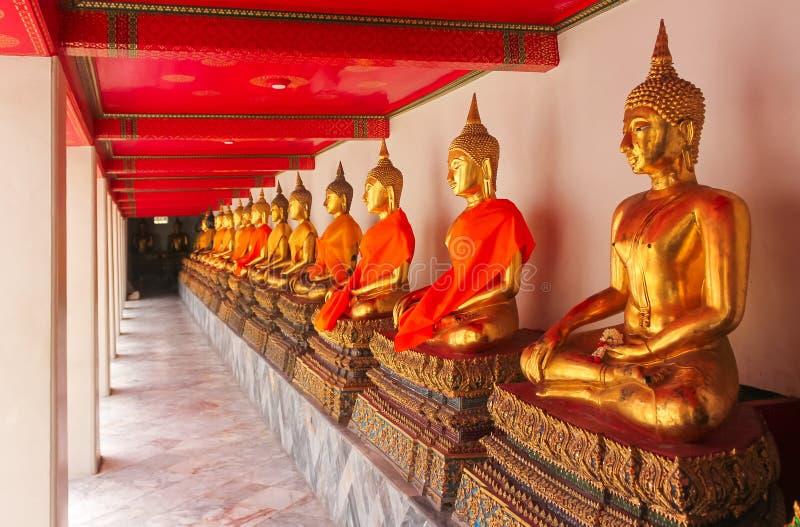 Fila de las estatuas de oro de Buda en Wat Pho, templo del Buda de oro de descanso fotografía de archivo libre de regalías
