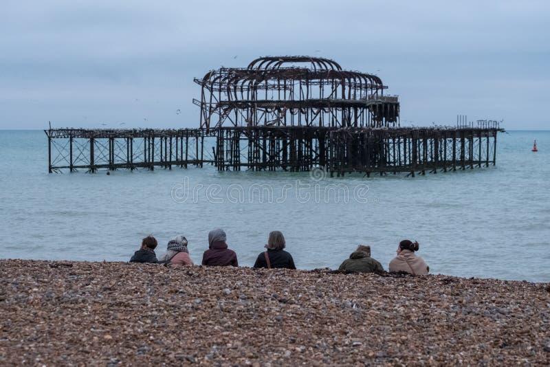 Fila de las mujeres que se sientan en la playa guijarrosa en Brighton Reino Unido en una tarde hivernal en diciembre, delante de  fotos de archivo libres de regalías