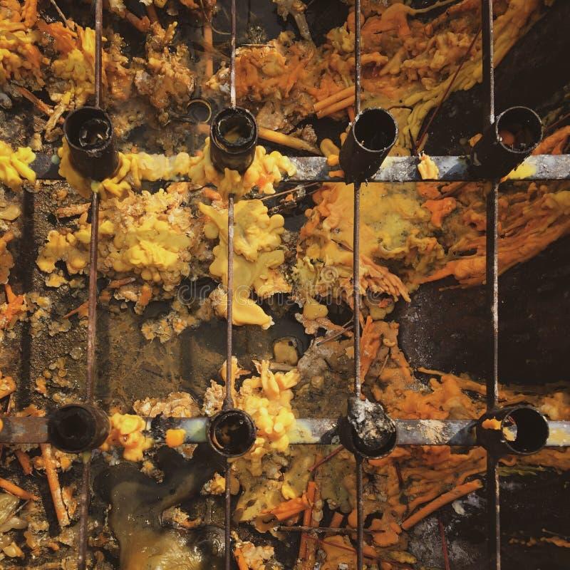 Fila de las palmatorias de acero sobre vela amarilla y anaranjada derretida en el templo en Tailandia imagen de archivo