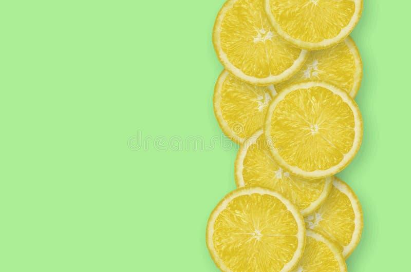 Fila de las rebanadas amarillas de la fruta cítrica del limón en fondo brillante de la cal imagen de archivo libre de regalías
