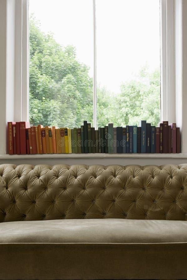 Fila de libros en alféizar con Sofa In Foreground imagen de archivo